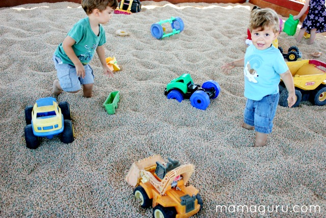 Two boys play with Tonka trucks in a dried bean pit, like a sandbox.