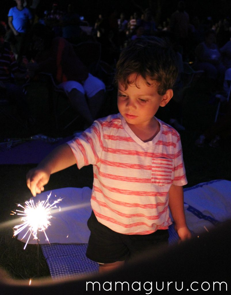 Boy in red and white striped shirt holds a sparkler on the 4th of July for summer fun