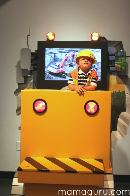 Little boy wears construction hat at a museum construction exhibit