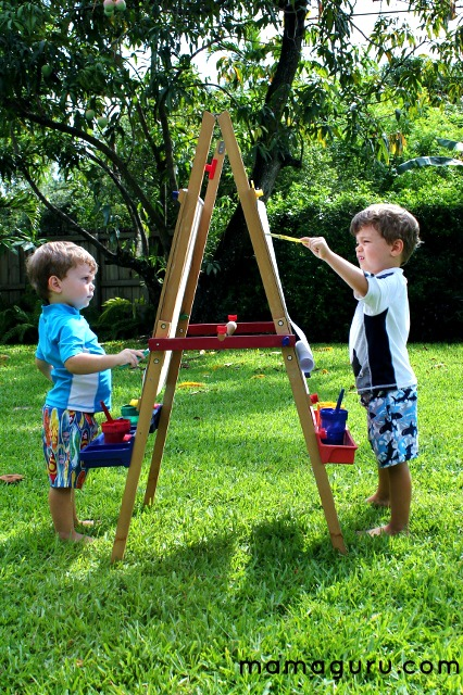 Children paint on an easel outdoors.